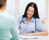 Smiling doctor or nurse with patient royalty free stock photo