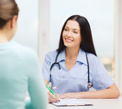 Smiling doctor or nurse with patient Stock Image