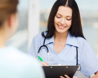 Smiling doctor or nurse with patient Royalty Free Stock Photos