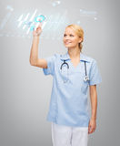 Smiling doctor or nurse pointing to cardiogram Royalty Free Stock Photo