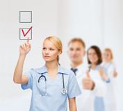 Smiling doctor or nurse pointing to checkmark Stock Photo