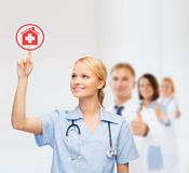 Smiling doctor or nurse pointing to hospital icon Royalty Free Stock Image