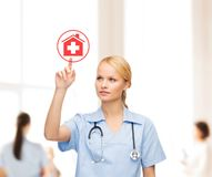 Smiling doctor or nurse pointing to hospital icon Stock Photos
