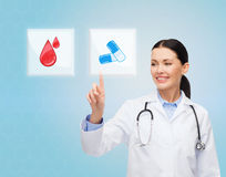 Smiling doctor or nurse pointing to pills icon. Healthcare, medicine, people and technology concept - smiling young doctor or nurse pointing to icon or pressing Royalty Free Stock Image