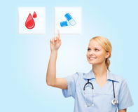 Smiling doctor or nurse pointing to pills icon Royalty Free Stock Photo