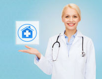 Smiling doctor or nurse pointing to pills icon Royalty Free Stock Images