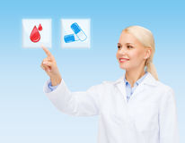 Smiling doctor or nurse pointing to pills icon Royalty Free Stock Photos