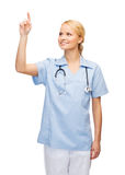 Smiling doctor or nurse pointing to something Royalty Free Stock Images
