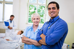 Smiling doctor and nurse standing with arms crossed Stock Photos