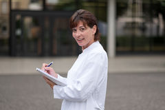 Smiling doctor or nurse taking notes Royalty Free Stock Photos