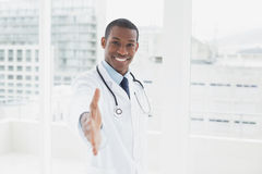 Smiling doctor offering a handshake in a medical office Stock Photo