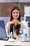 Smiling doctor at office desk Royalty Free Stock Photo