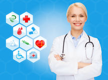 Smiling doctor over medical icons blue background Stock Photography