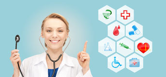Smiling doctor over medical icons blue background Stock Image