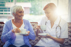 Smiling doctor and patient having tea Stock Photo