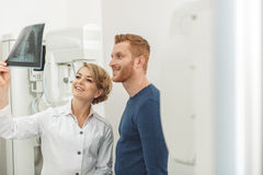Smiling doctor and patient looking at x-ray stock image