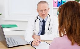 Smiling doctor with patient in medical office royalty free stock photos
