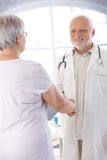 Smiling doctor and patient shaking hands Royalty Free Stock Photography