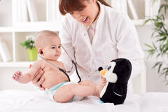 Smiling doctor pediatrician playing and enjoy with baby patient Royalty Free Stock Photography