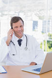 Smiling doctor phoning in his office Stock Photo