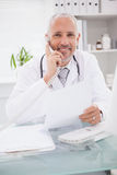 Smiling doctor phoning and using computer Royalty Free Stock Photography