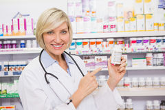 Smiling doctor pointing a drug bottle Royalty Free Stock Photos