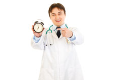Smiling doctor pointing finger on alarm clock Stock Photography