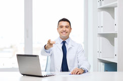 Smiling doctor pointing finger at you in office Stock Images