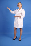 Smiling Doctor Pointing To Her Right Royalty Free Stock Images