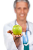Smiling doctor presenting a green apple Royalty Free Stock Photo