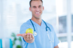 Smiling doctor presenting a green apple Royalty Free Stock Photos