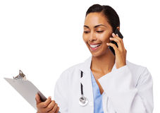 Smiling Doctor Reading Clipboard While Using Smart Phone Stock Image