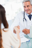 Smiling doctor shaking hands with his patient Stock Photo