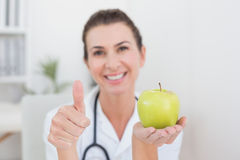 Smiling doctor showing apple with thumbs up Royalty Free Stock Image