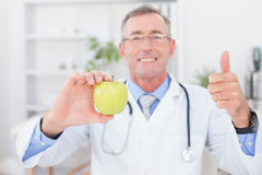 Smiling doctor showing apple with thumbs up Stock Images