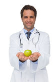 Smiling doctor showing apple to camera. On white background Royalty Free Stock Image