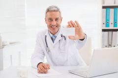 Smiling doctor showing a blank Royalty Free Stock Image
