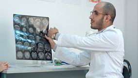 Smiling doctor showing brain computed tomography x-ray image to his patients royalty free stock photos