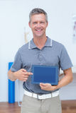 Smiling doctor showing digital tablet. In medical office Stock Photo