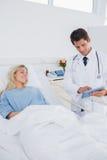 Smiling doctor showing digital tablet Stock Photo