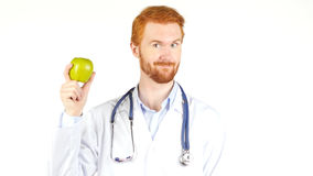 Smiling  Doctor showing green apple to the camera Royalty Free Stock Images