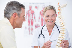 Smiling doctor showing her patient a spine model Stock Image