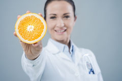 Smiling doctor showing a juicy orange Royalty Free Stock Photos