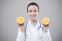 Smiling doctor showing a juicy orange Stock Photos