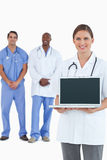 Smiling doctor showing laptop with colleagues behind her Royalty Free Stock Image