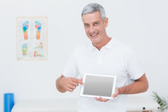 Smiling doctor showing laptop pc. In medical office Stock Photos