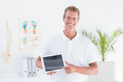 Smiling doctor showing laptop pc. In medical office Royalty Free Stock Photos