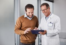 Smiling doctor showing man documents with recommendations. Waist up portrait of smiling medical adviser telling for male patient about survey results stock photography