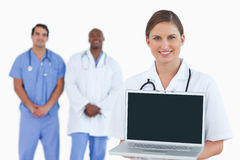 Smiling doctor showing notebook with colleagues behind her Stock Photography