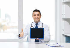 Smiling doctor showing tablet pc and thumbs up Stock Photos
